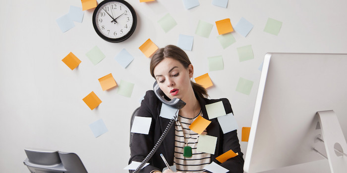 multitasking women with too many post-it notes.
